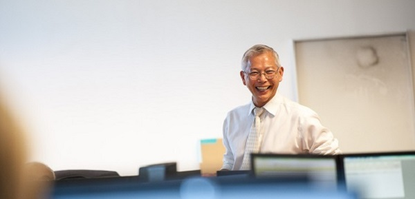Man standing in office laughing